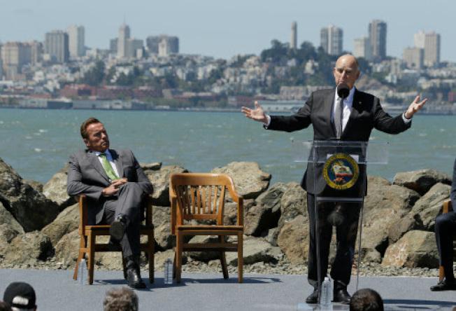 去年7月布朗州長在金銀島簽署氣候法案前發表演講,前州長阿諾史瓦辛格在場聆聽。(美聯社)
