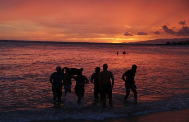 8月底颶風雷恩來襲之前,遊客在檀香山海灘戲水,欣賞夕陽。(美聯社)