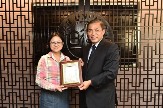 總會長梁義大(右)致贈上海市台聯會長盧麗安奬牌。(台親會提供)