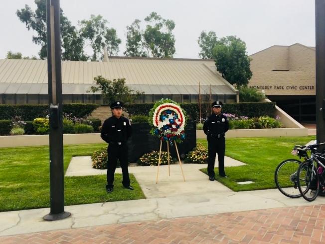 蒙市警消人員捧著花圈獻給逝世的警消人員。(記者林佩錦/攝影)