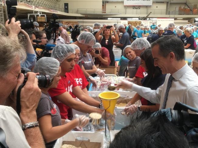 賈西提(右一)加入志工們行列,邊包裝食物、邊隨著音樂不停擺動,展現十足親和力。(記者謝雨珊/攝影)