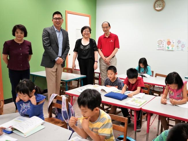 華美銀行的代表在華夏中文學校理事長馬莎(後立左一)、總校校長唐藝傑(後立右二)陪同下,參觀華夏中文學校的課堂。(記者賈忠/攝影)