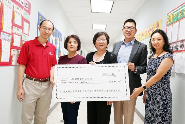華美銀行代表劉謙義(右二)、林起湧(左一)向華夏中文學校理事長馬莎(左二)、總校校長唐藝傑(左三)、周日校長沙莎(右一)捐款5000元支票。(記者賈忠/攝影)