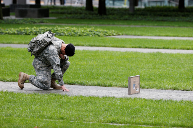 一位陸軍後備士官艾德溫11日為在九一一世貿大救災犧牲的表哥、紐約市消防員柯端拉的遺像下跪致哀。(路透)