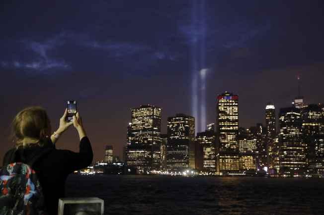 從紐約市布碌崙隔著東河遠眺曼哈頓南端,11日晚出現兩道強烈光束照亮夜空,以「致哀之光」紀念9/11恐襲事件17周年。(路透)