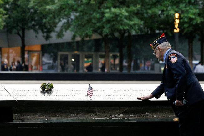一位退休警官在九一一紀念池旁插上國旗致敬。(路透)