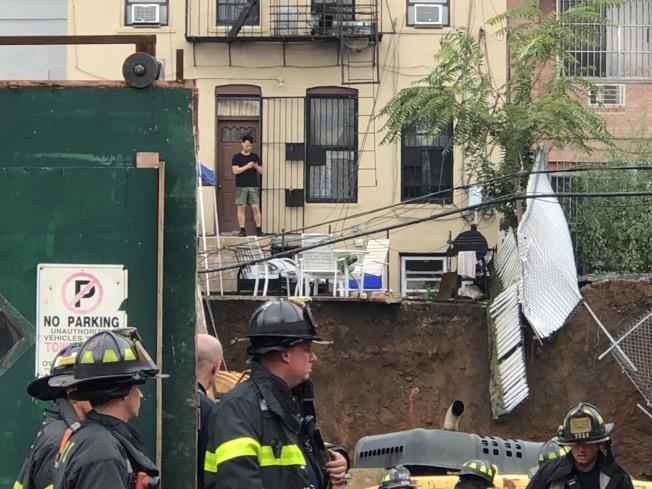 消防員冒雨搶救,被壓工人仍在險境。(記者洪群超/攝影)