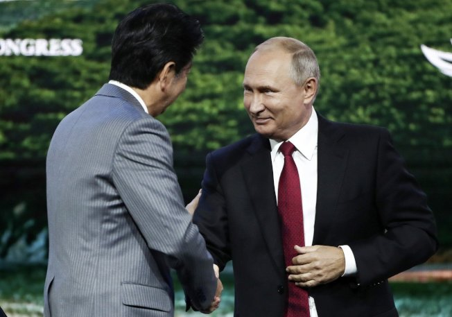 俄羅斯總統普亭(右)與日本首相安倍晉三(左)握手。 (美聯社)