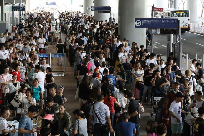 大阪關西機場4日受到颱風燕子的影響,一條跑道淹水,加上郵船撞毀這座人工島的對外聯絡橋梁,造成機場內旅客受困。圖為旅客5日在關西機場排隊等待專車。Getty Images