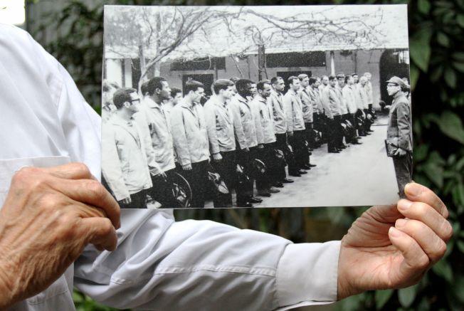 「河內希爾頓」的典獄長拿著當年美軍戰俘的黑白照片。(Getty Images)