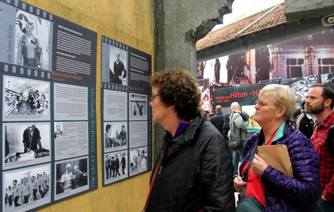 參觀戰俘營的遊客仔細閱讀有關馬侃的圖片。(Getty Images)