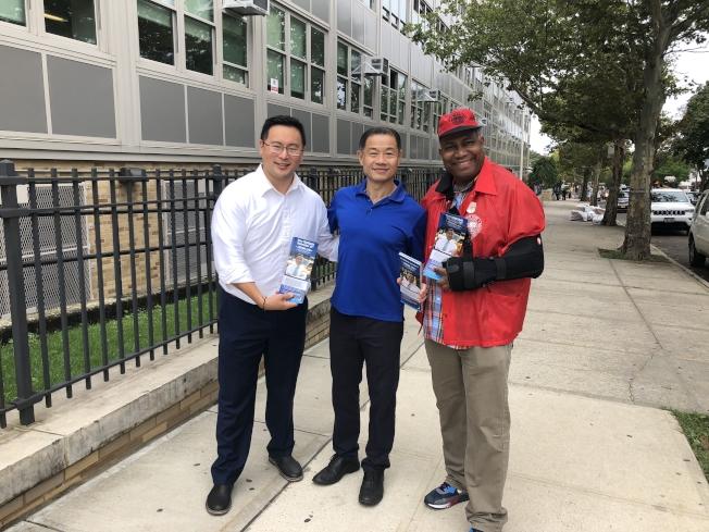 劉醇逸(中)與金兌錫(左)在投票站外問候選民。(記者陳小寧/攝影)