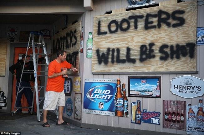 北卡店主把商店門窗釘上保護狂風的木板,上面寫著「打劫者,格殺勿論」。(Getty Images)