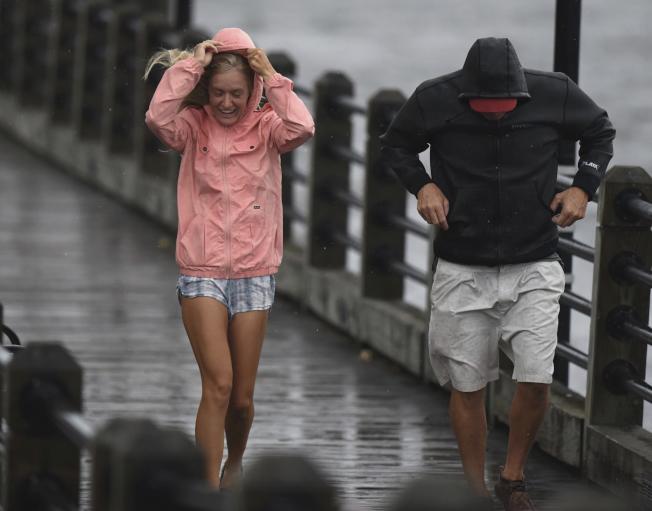 一對父女13日下午在北卡威明頓市中心步行,感受到颶風風力。(美聯社)