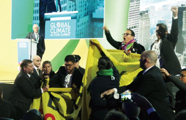 峰會場內有人拉起橫幅抗議,台上致辭者(左)為紐約前市長彭博。(記者李晗/攝影)
