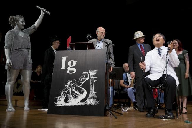 2018年搞笑諾貝爾獎13日在哈佛大學舉行頒獎典禮,日本醫師堀內秋良(右)提出為自己照大腸鏡的革命新方法而獲獎。(美聯社)