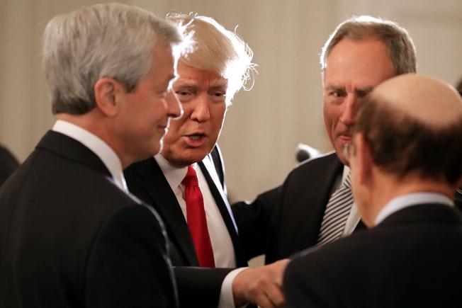 針對摩根大通執行長戴蒙(左一)發表競選總統的言論,川普(左二)13日反擊,稱戴蒙「沒有那種天賦或智慧」。圖為兩人去年2月在白宮一項活動上和其他企業界人士交流。(Getty Images)