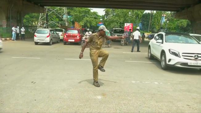為了解決交通亂象,一名印度交警指揮時加入自己獨特的舞步,讓好奇的用路人放慢車速,進而遵從他的指揮。路透