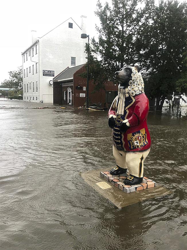 佛羅倫斯颶風引發的洪水,造成美國北州數百位民眾住宅四周遭淹沒而孤立無援,當地救難人員今天緊急展開救援行動。圖為北卡新伯恩一個熊雕塑底遭水淹。美聯社