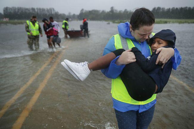 民間義工組成的救援隊從被淹的住宅中救出兒童。(Getty Images)