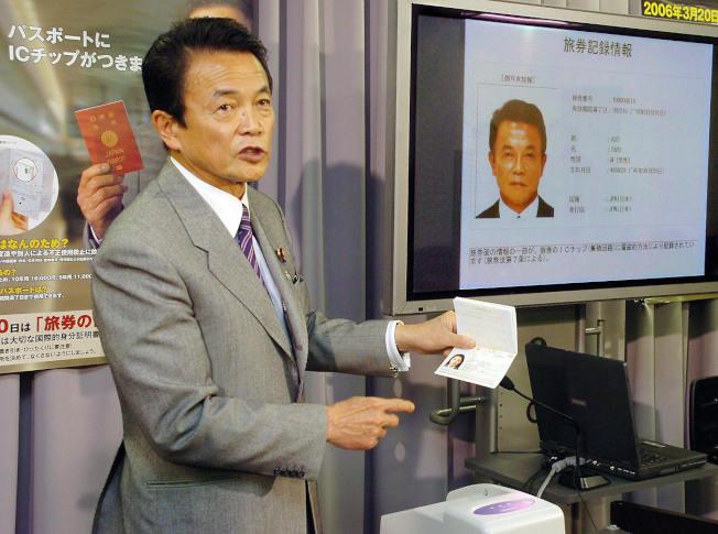 日本在全球護照指數排名第一,圖為時任外相的麻生太郎在2006年介紹嵌入電子晶片的日本護照。(Getty Images)