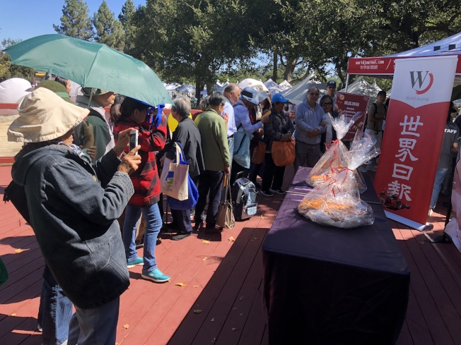 許多民眾提前30、40分鐘就到現場排隊等著吃大月餅,讓活動提早15分鐘開始。(記者林亞歆/攝影)