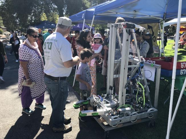 機器人團隊在攤位上展示作品,並向民眾介紹機器人功能。(記者林亞歆/攝影)