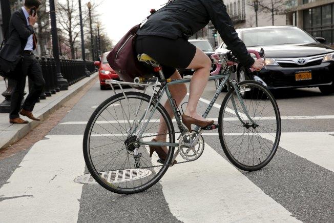 美國勞工選擇多元方式通勤,圖為華盛頓一名女性上班族穿高跟鞋騎腳踏車通勤。(路透)