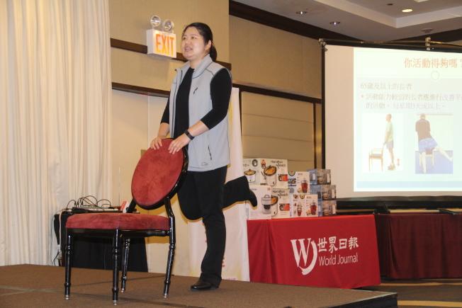 鄒文娟示範使用椅子練習平衡力。(記者賴蕙榆/攝影)