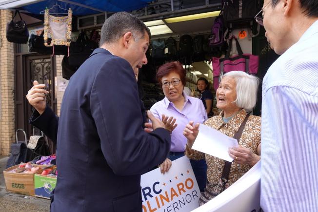 莫利拉羅(左)在華埠街頭與民眾互動。(記者金春香/攝影)