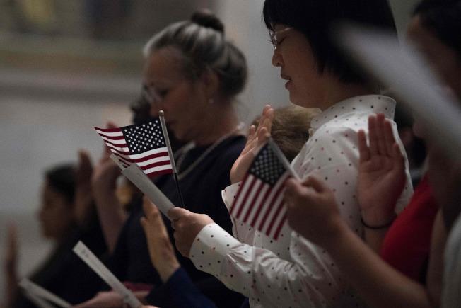 為防止新移民成為美國的負擔,國安部10月1日起實施新規,濫領福利者除無法領取綠卡外,更有可能遭遞解。圖為新移民舉著小國旗宣誓入籍。(美聯社)