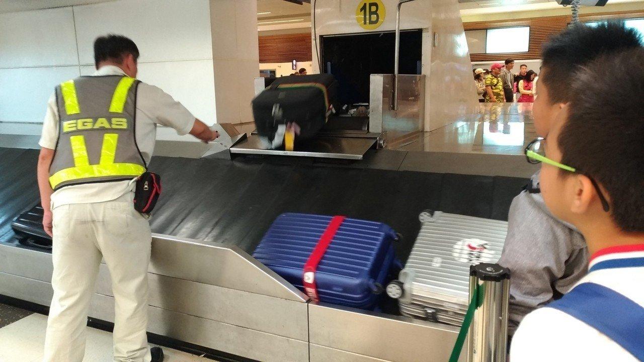工作人員正在將行李整理好,提把向上方便旅客提取。圖/記者楊德宜攝
