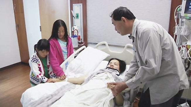 周翠瑩兩年前被樹枝擊中,下半身癱瘓,被送到醫院,丈夫和兩個女兒在旁。(本報檔案照)