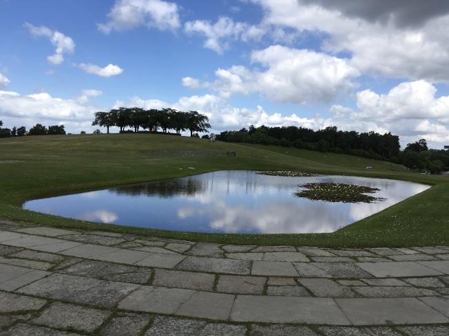 遠方土丘,是冥想山丘,山丘頂那叢樹圍著的是祭壇。這墓園的設計者就長眠在蓮池邊。
