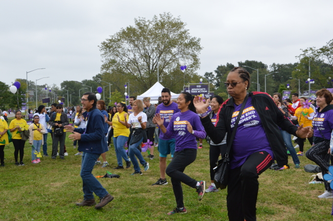 王肯尼(前排藍衣舞者)和其餘參賽者,在健走前跳健身操熱身。(記者牟蘭/攝影)