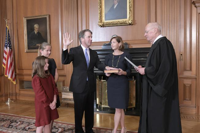 經過激烈抗爭後,卡瓦諾法官6日晚宣誓就職為新的聯邦大法官,參院雖以兩票之差,通過任命。但美國政治傷痕難以癒合。圖為退休的大法官甘迺迪6日晚主持宣誓。(美聯社)