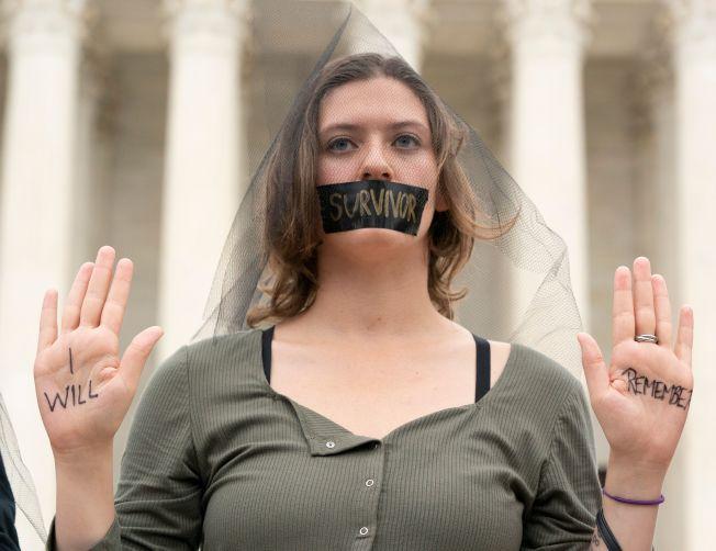 抗議者以黑布封口,表示婦女含冤,不滿卡瓦諾成為聯邦高院大法官,抗爭激烈持續,美國政治傷痕難以癒合。(Getty Images)