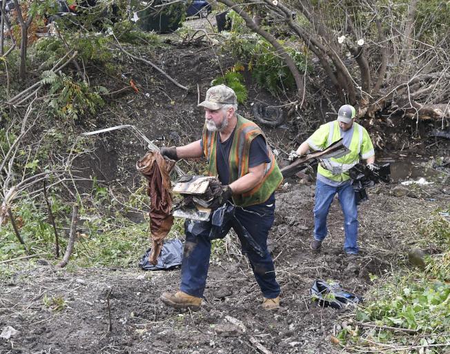 鑑識人員在現場收集殘骸證據。(美聯社)