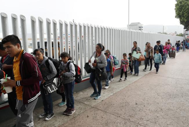 政庇獲准者可以享受公共福利。圖為7月26日人們排隊在墨西哥入境美國附近申請庇護。(美聯社)