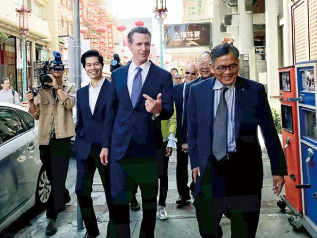 紐森(中)在建築師劉運方(左)、中華總商會會長區國雄(右)等陪同下走訪華埠。(記者李秀蘭/攝影)