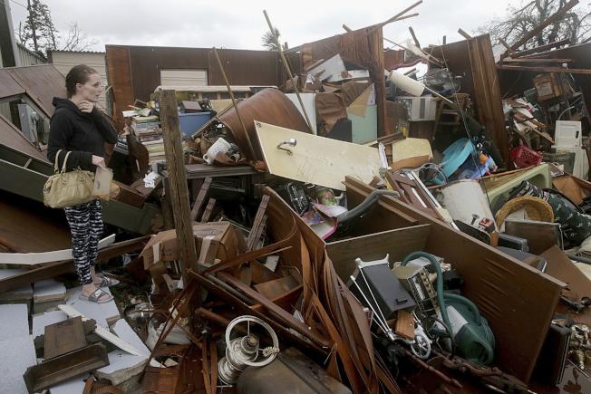 圖為佛羅里達州巴拿馬市一名女子查看災損情況。(美聯社)
