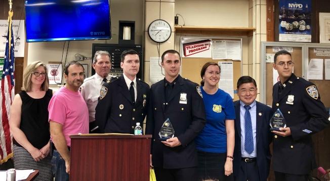 """夏因(左四)向两名警员颁发""""本月最佳警员""""奖牌。(记者朱蕾�u摄影)"""