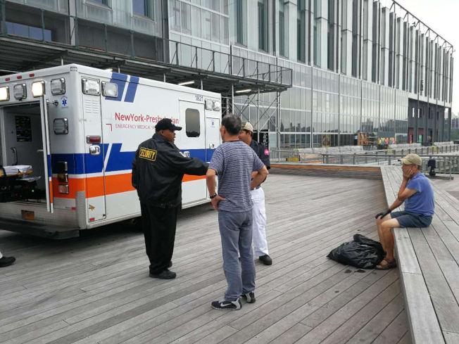 鄭姓拾荒華男( 右)被毆打後送上救護車。(讀者提供)