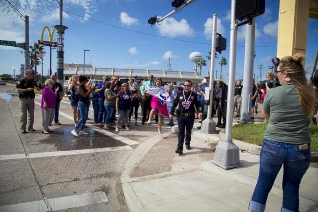 布拉佐里亞縣警局第一分局長薩克和同事打賭輸了之後,願賭服輸換上女裝上街亮相,吸引許多民眾圍觀並要求合影。(取自自由港市警局臉書)
