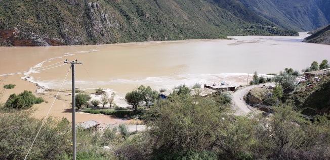 西藏自治區昌都市江達縣11日發生山體滑坡,導致金沙江斷流並形成堰塞湖。圖為金沙江水位上漲,淹沒當地民房。 中新社