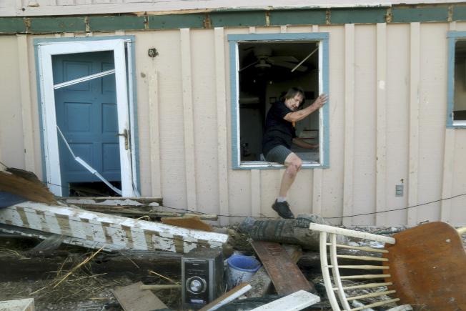 居民從毀損的家中跨出來。美聯社