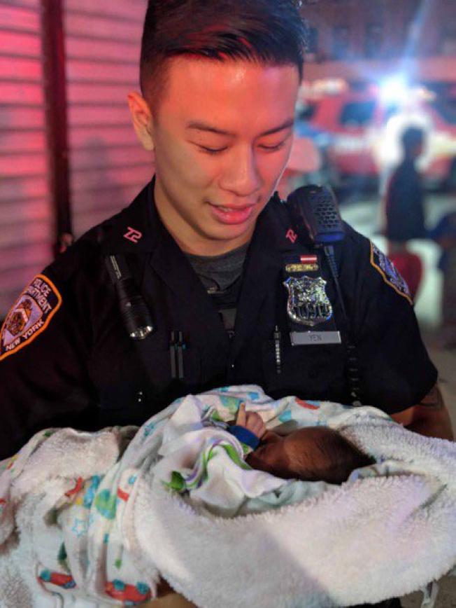 顏麥克(Michael Yen)抱著剛剛被解救出的襁褓嬰兒。(市警提供)