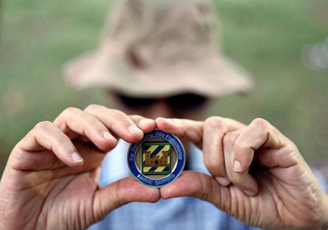 一名伊拉克移民展示美國軍方頒給他的獎章。(路透)