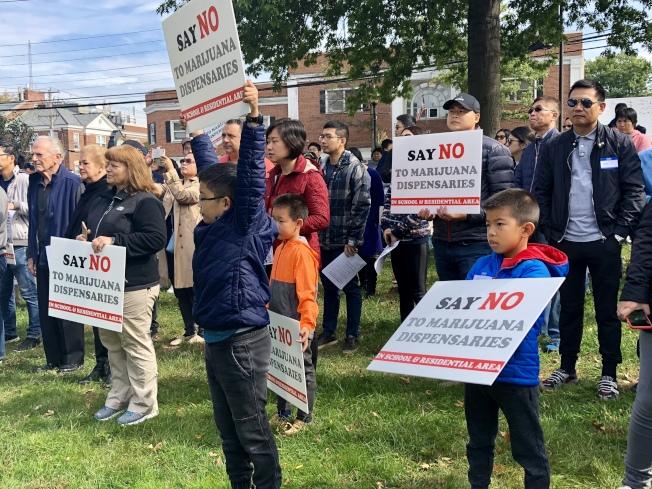 小朋友手舉反對醫用大麻藥房開在學校和居民區附近的標語。(記者朱蕾/攝影)
