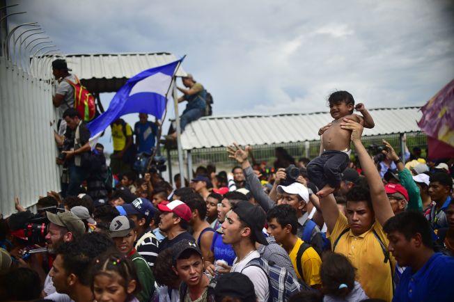 數千名中美洲移民今天湧入瓜地馬拉西北部邊界,現場可見移民將嬰兒高舉過頭接力傳遞。Getty Images